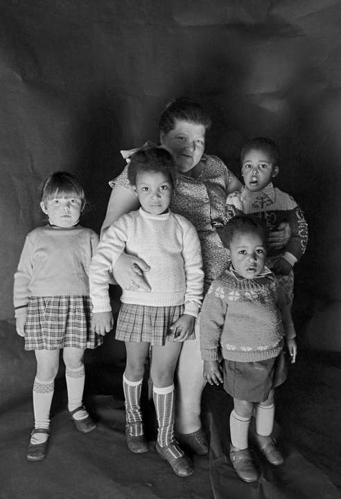 Daniel Meadows: Portrait of a foster mother with children in Meadows's free photographic studio on Greame Street, Moss Side, Manchester, February - April 1972